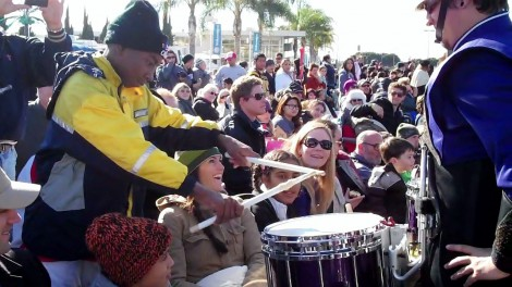 A WCU drummer gives his drumsticks to a Rose Parade-goer and invites him to play the drum during a parade break.