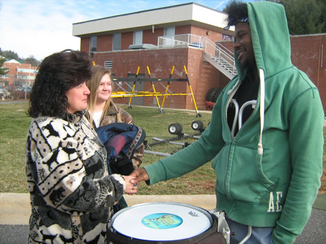 Justin Holmes, a sophomore who plays snare drum in the Western Carolina University Pride of the Mountains Marching Band, greets Beverly Pruett (left), whose son Billy Epley played snare drum in the band when he died in 2005.