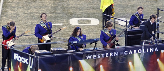 "Dustin Painter (far right) coordinates electronics and sings through the vocoder during the field show ""Rock U."""
